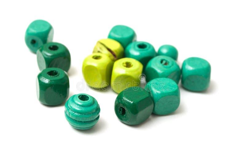 Green wooden beads on white background. Closeup of green wooden beads on white background royalty free stock photos