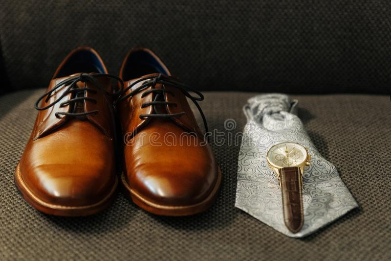 Closeup of groom`s shoes, watches and tie. getting readyÑŽ dark background. Closeup groom`s shoes, watches and tie. getting ready. dark background stock photography