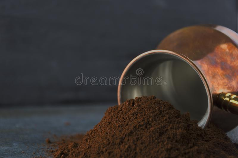 Closeup of ground coffee against coffee pot and dark wall royalty free stock photography