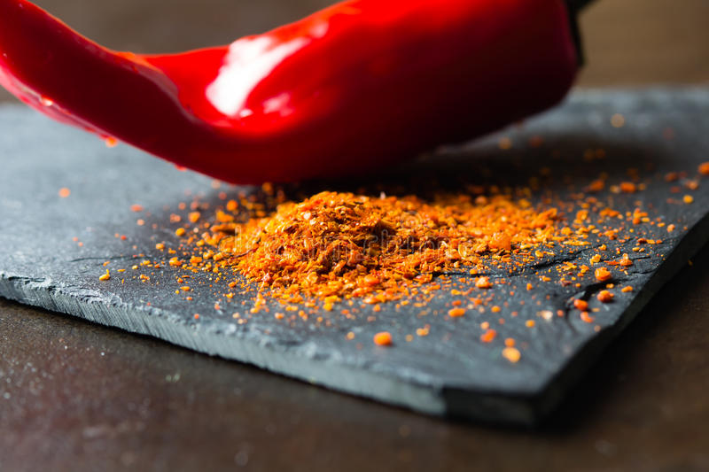 Closeup of ground dry pepper with fresh chili on background. Ground dry red pepper on stone board with fresh chili on background. Closeup royalty free stock image