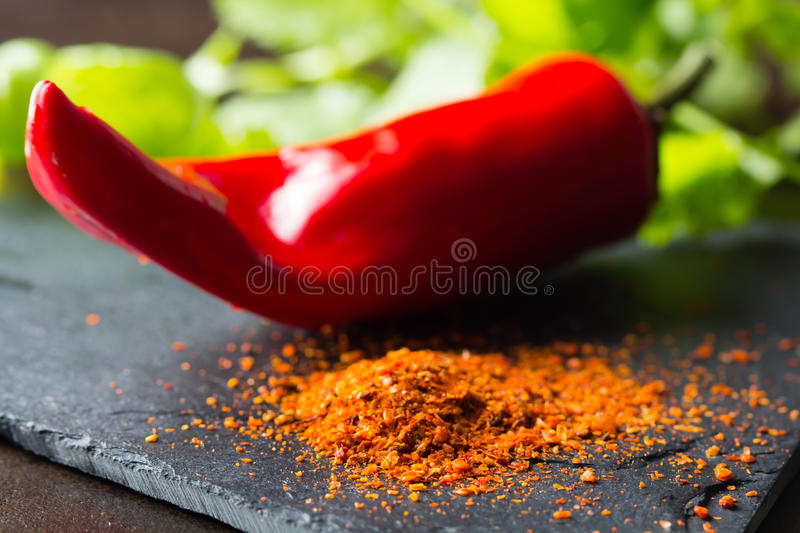 Closeup of ground dry pepper with fresh chili on background. Ground dry red pepper on stone board with fresh chili on background. Closeup stock images