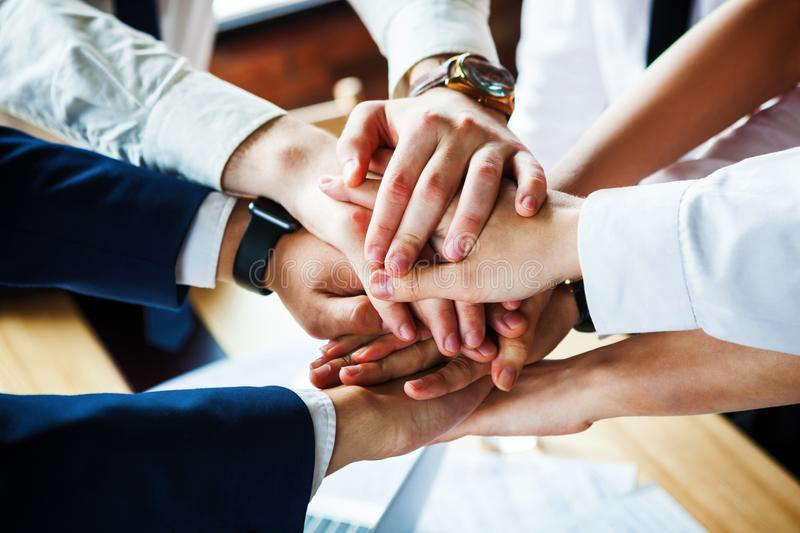 Closeup of a group of businesspeople joining their hands together. stock image