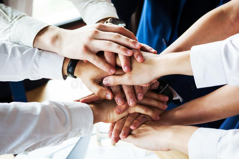 Closeup of a group of businesspeople joining their hands together. royalty free stock photography