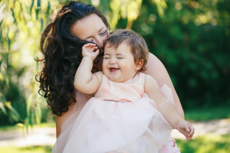 Closeup group portrait of beautiful white Caucasian brunette mother holding laughing baby daughter kissing her in cheek royalty free stock photos