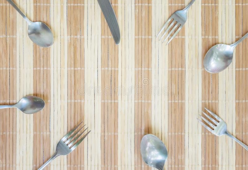 Closeup group of stainless fork spoon and knife on wood mat textured background with copy space at the center in top view. Closeup group of stainless fork spoon royalty free stock image