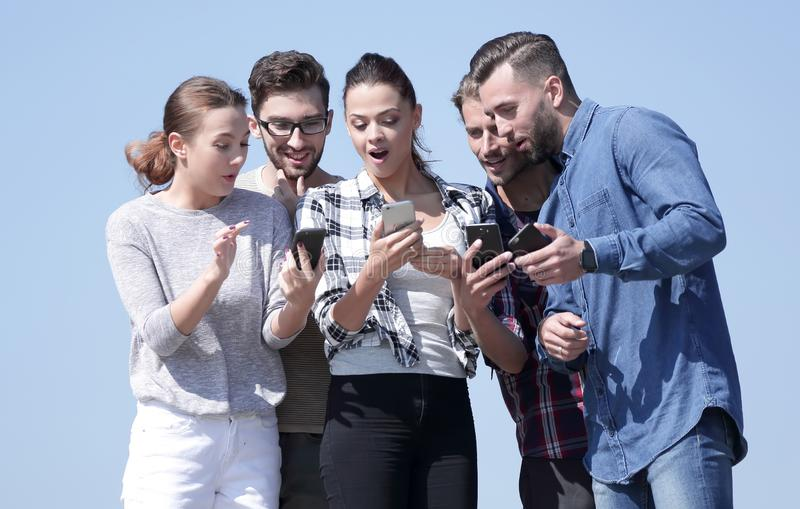 Closeup. the group of students using smartphones. On a blue background royalty free stock photo