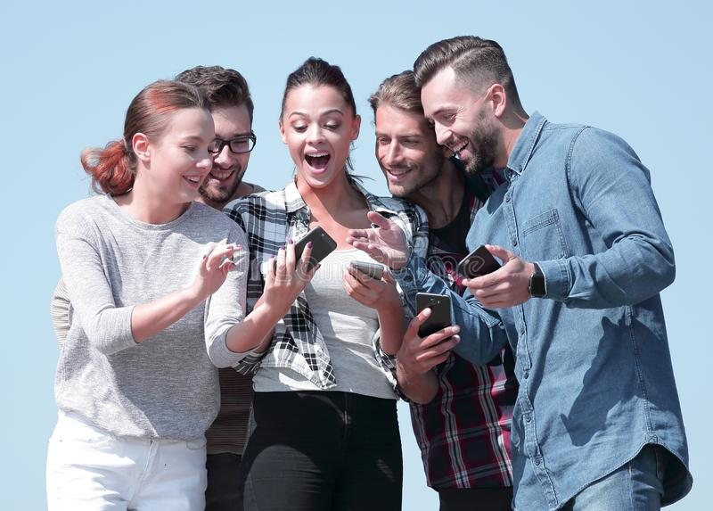 Closeup. the group of students using smartphones. Isolated on a blue background royalty free stock images