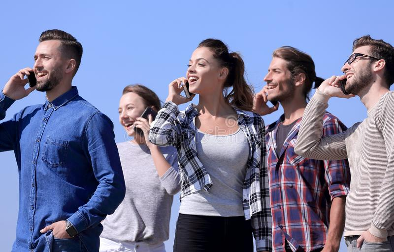 Closeup of a group of young people with smartphones. stock photos