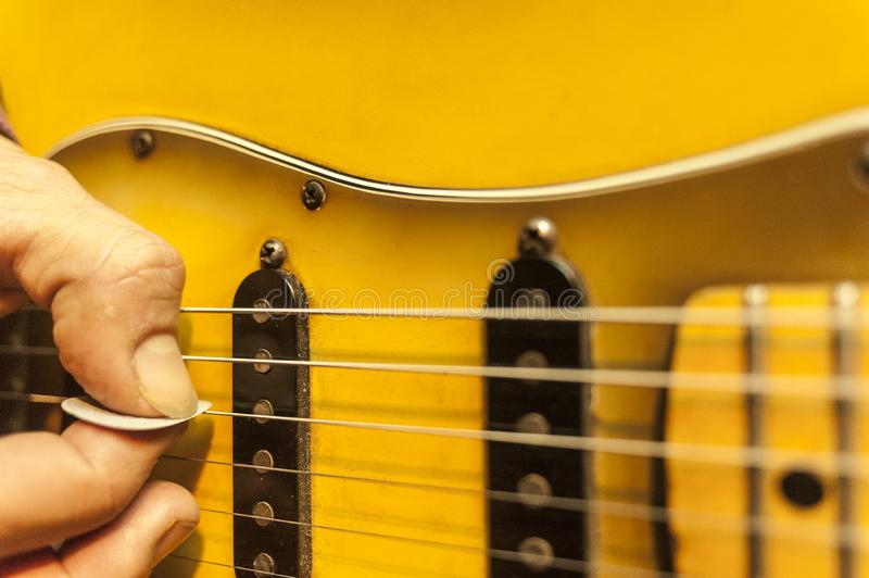 Closeup of guitarist fingers holding plectrum on strings of electric guitar royalty free stock images