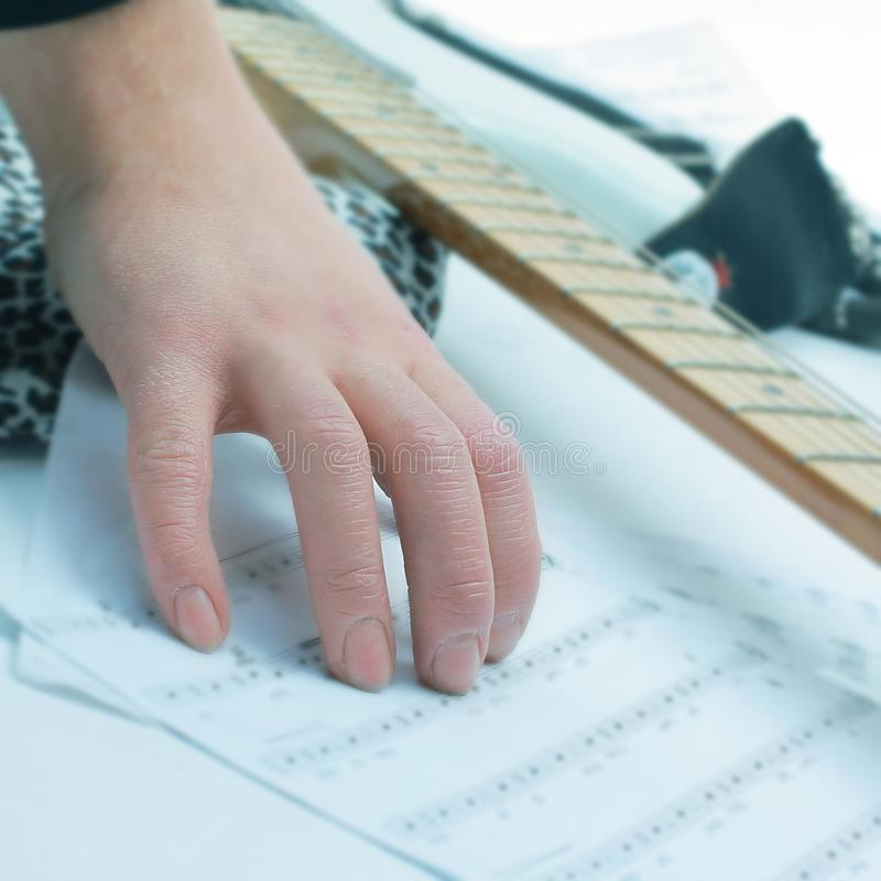 Closeup of a guitarist touching sheet music .isolated on a whit. E background.photo with copy space royalty free stock images