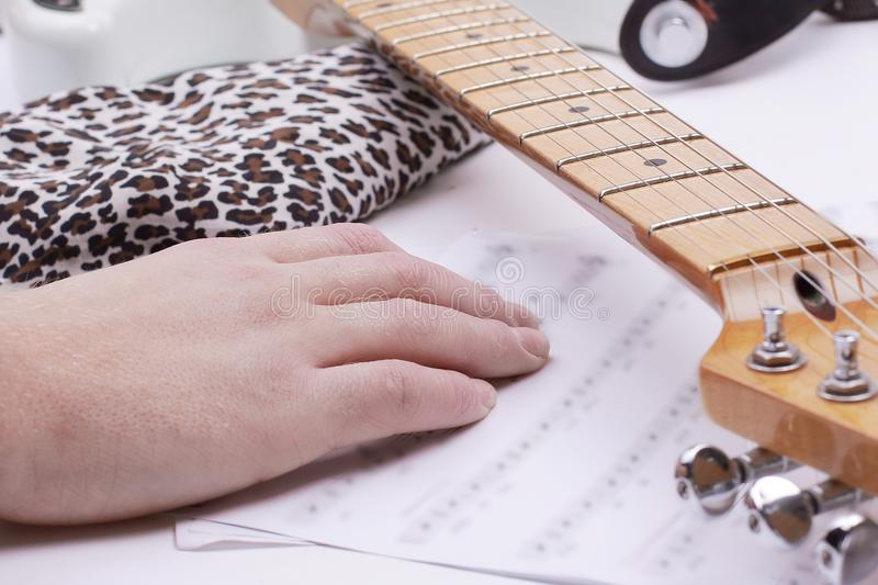 Closeup of a guitarist touching sheet music .isolated on a whit. E background.photo with copy space stock photography