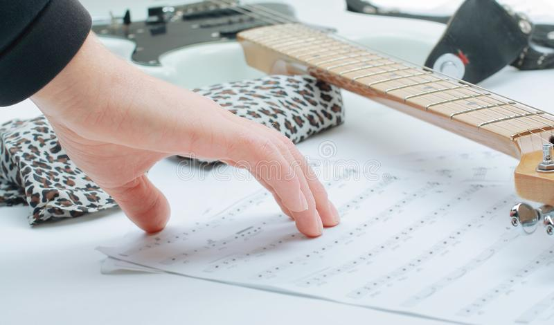 Closeup of a guitarist touching sheet music .isolated on a white background. Photo with copy space stock photography