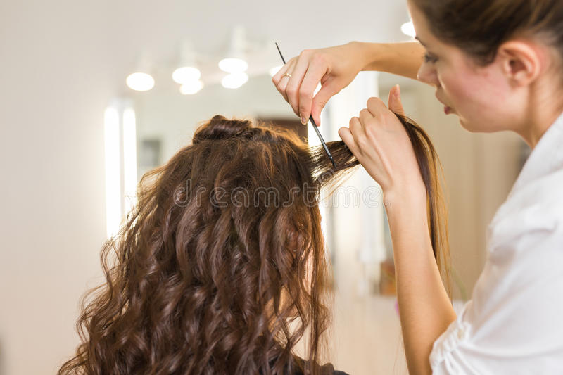 Closeup hairdresser coiffeur makes hairstyle. royalty free stock image