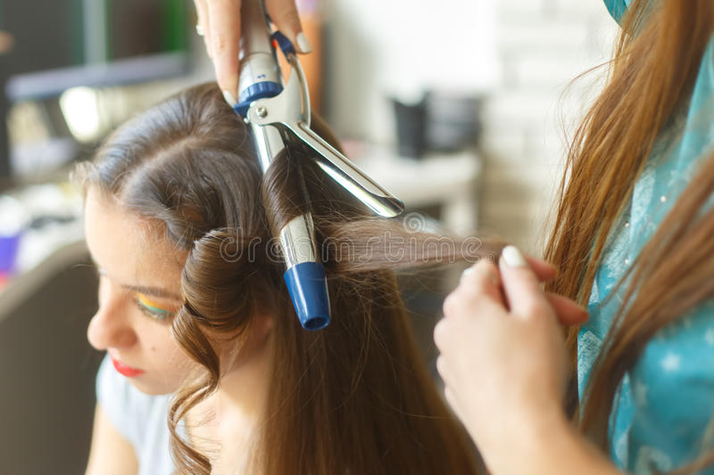 Closeup of hairdresser doing the styling for a festive evening of wedding hairstyles woman with long black hair. Hairdresser makes curles using curling iron royalty free stock image