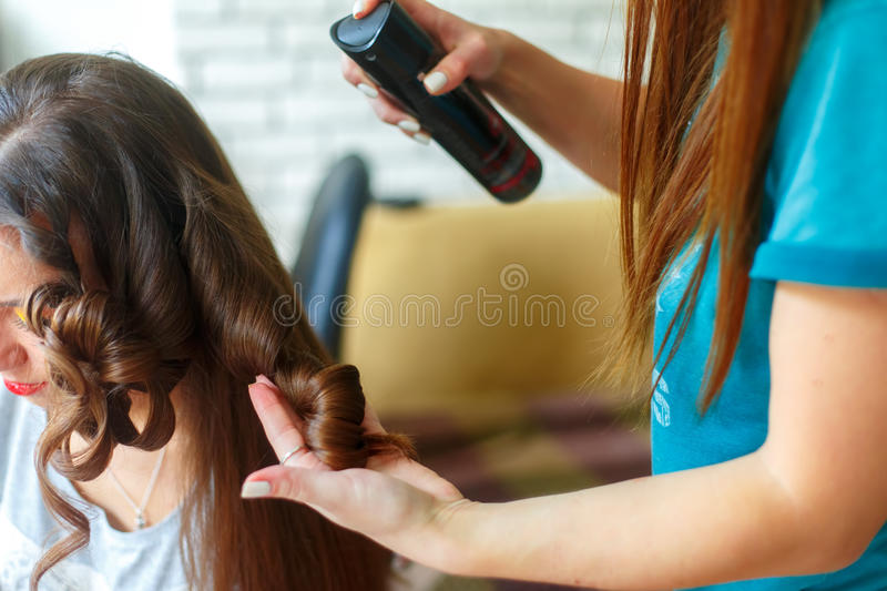Closeup of hairdresser doing the styling for a festive evening of wedding hairstyles woman with long black hair. Hairdresser makes curles using hairspray royalty free stock image