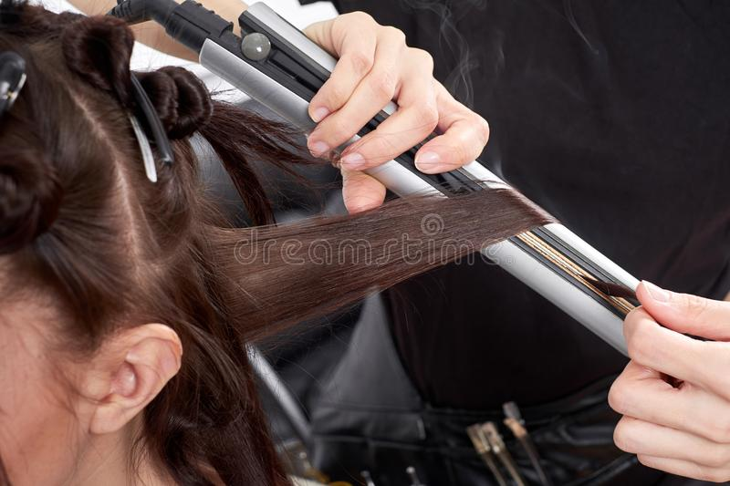 Closeup hairdresser makes hairstyle for young woman in beauty salon stock photo