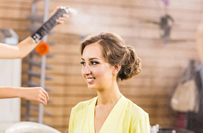 Closeup of hairdresser's hands using hairspray on client's hair at salon. stock photo