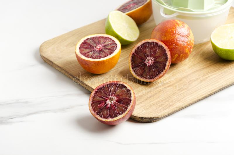 Closeup of half blood oranges and lime on the cutting board, manual juicer.Preparation of fresh tasty juice stock image