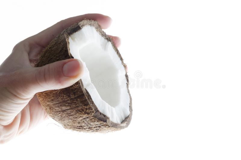 Closeup of half cococnut and girl`s hand against white surface.Cosmetics concept. Woman holding fresh delicious coconut against white surface Closeup of half stock photo