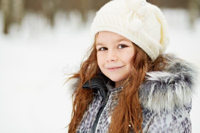 Closeup half-turned portrait of little girl in grey jacket stock image