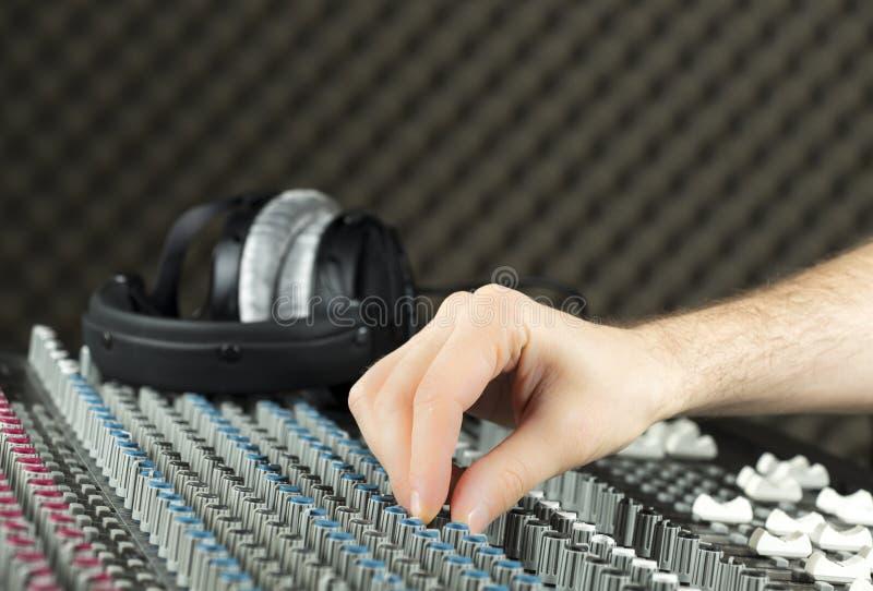 Closeup of a hand adjusting a studio mixer stock photo