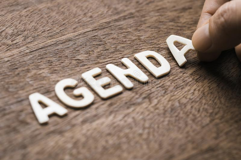 Agenda Wood Letters. Closeup hand arrange wood letters as AGENDA word royalty free stock photography