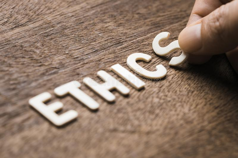 Ethics Wood Letters. Closeup hand arrange wood letters as ETHICS word royalty free stock photography