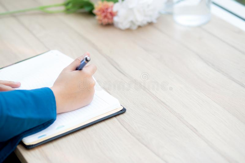 Closeup hand asian woman sitting study and learning writing notebook and diary on table in at cafe shop. Girl homework, business writer female working on table royalty free stock images