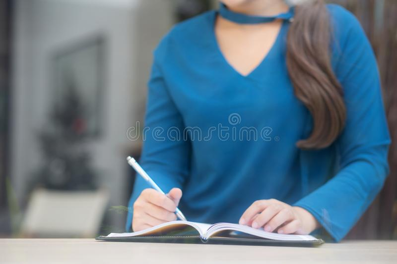 Closeup hand asian woman sitting study and learning writing notebook and diary on table in at cafe shop. Girl homework, business writer female working on table stock images