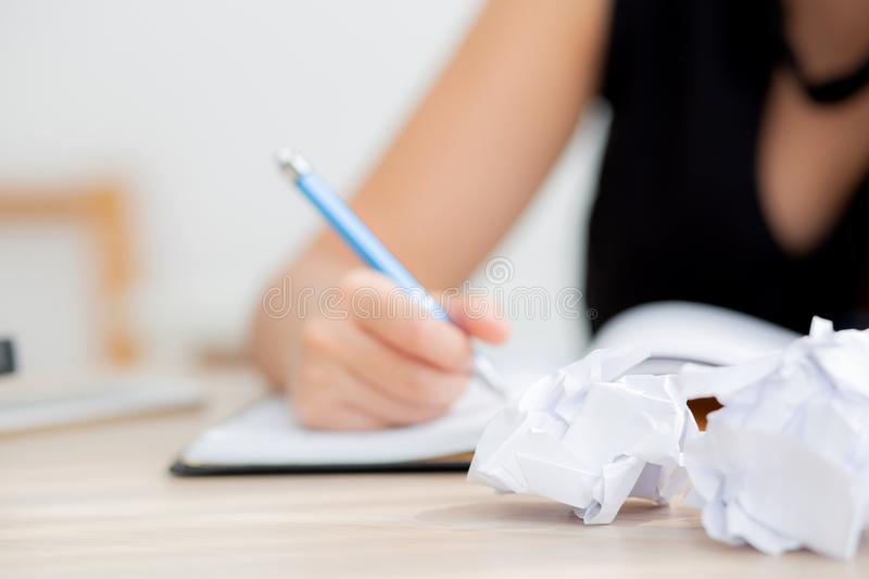 Closeup hand asian woman writer thinking idea and writing on notebook or diary with happy on desk office stock image