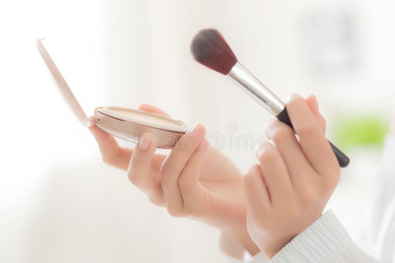 Closeup hand of beauty young asian woman with face looking mirror applying makeup with brush cheek in the bedroom royalty free stock image