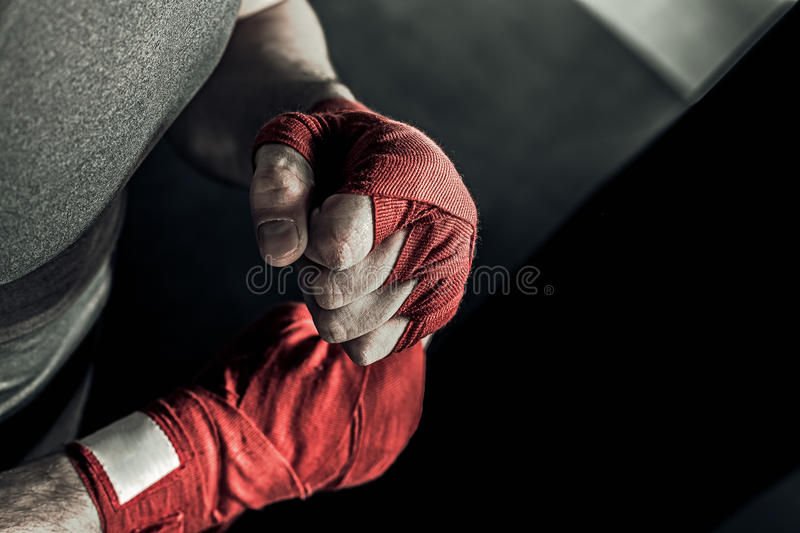 Closeup hand of boxer with red bandages. Closeup male hand of boxer with red boxing bandages. Fists of fighter before the fight or training in sport gym royalty free stock photos