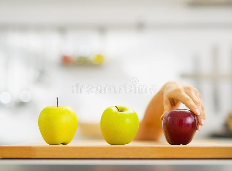 Closeup on hand choosing between two green and one red apple stock images