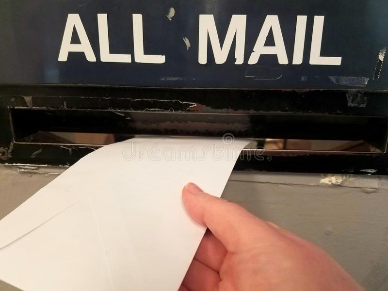 Mailing a letter in the mail slot at the post office stock photos