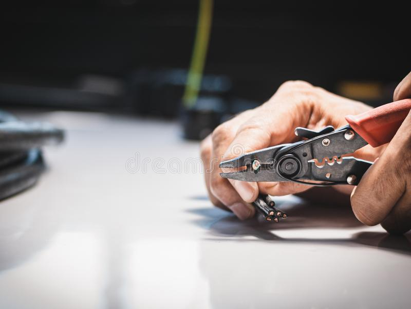 Electrician is using electrical stripping pliers royalty free stock image