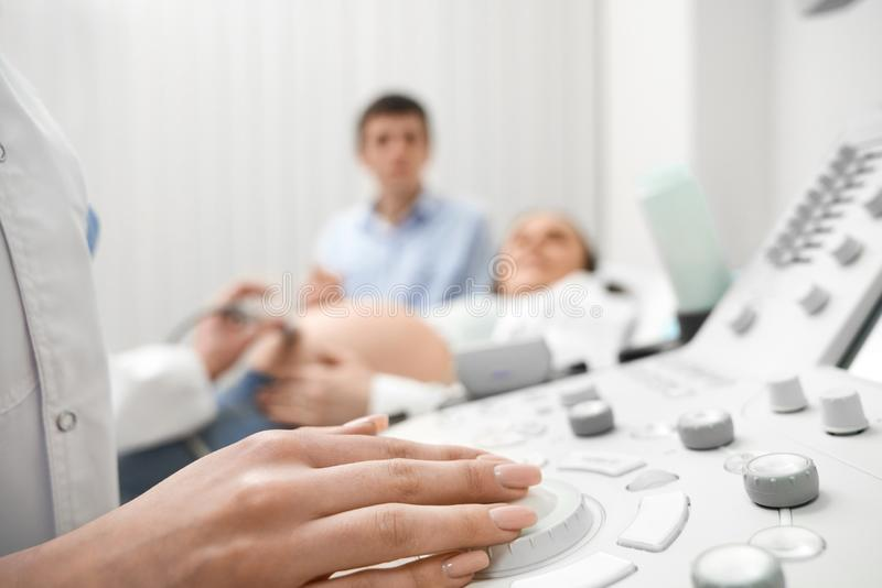 Closeup hand of female doctor on ultrasound machine stock photo