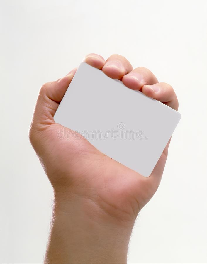 CLOSEUP OF HAND HOLDING A BLANK WHITE CREDIT CARD FACING CAMERA royalty free stock photography