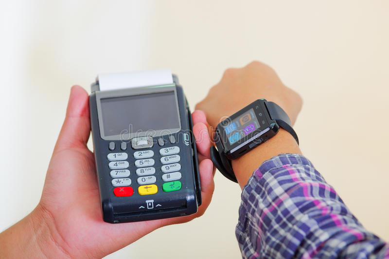 Closeup hand holding credit card payment terminal, another arm wearing smart watch with screen lit, white studio. Background royalty free stock image