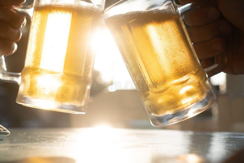 Closeup hand holding fresh lager beer mugs with sun rays. Closeup toast clinking fresh lager beer glasses mugs with sun rays in hot summer day royalty free stock image