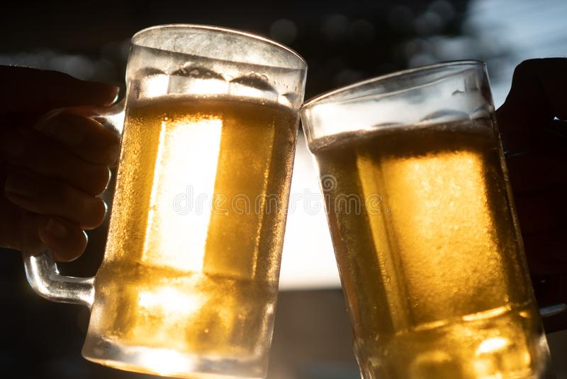 Closeup hand holding fresh lager beer mugs with sun rays. Closeup toast clinking fresh lager beer glasses mugs with sun rays in hot summer day royalty free stock photo