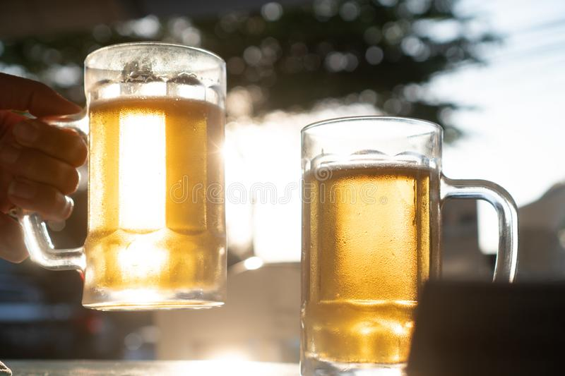 Closeup hand holding fresh lager beer mugs with sun rays. Closeup toast clinking fresh lager beer glasses mugs with sun rays in hot summer day stock photography