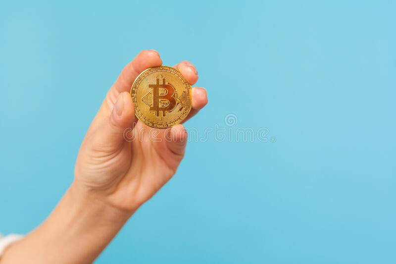 Closeup of hand holding golden bitcoin against blue background, advertising btc coin, copy space for cryptocurrency commercial. Digital money, electronic stock photos