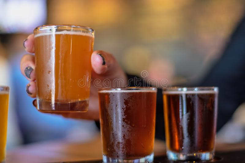 Closeup of hand holding a small sample beer glass stock images