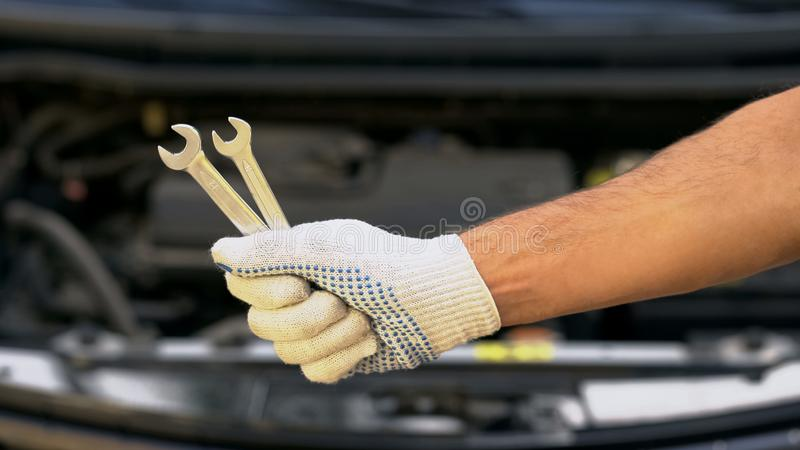 Closeup of hand holding spanners, repairing car in garage, upgrading vehicle stock image