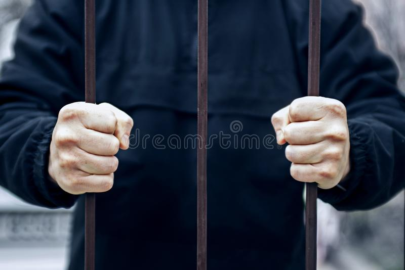 Closeup of a hand holding a steel cage, prisoner concept. Hands of the prisoner in jail. Hope to be free royalty free stock photo