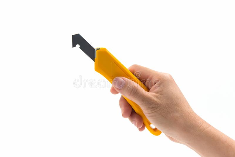 Closeup hand holding yellow plastic laminate cutter knife. Closeup hand holding yellow plastic laminate cutter knife on white background royalty free stock images