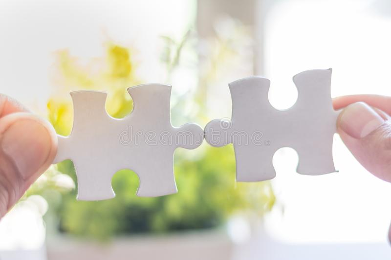 Closeup hand of man connecting jigsaw puzzle with sunlight effect, Business solutions, success and strategy concept,Comparative c. Oncept royalty free stock photo