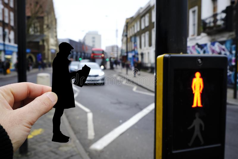 Silhouette of a man reading the newspaper, London. Closeup of the hand of a man holding a paper cutout in the shape of a man, wearing a flat cap and a coat royalty free stock image