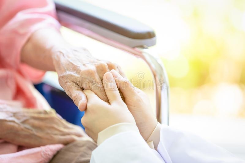 Closeup of hand medical female doctor or nurse holding senior patient hands and comforting her,.Caring caregiver woman supporting royalty free stock image