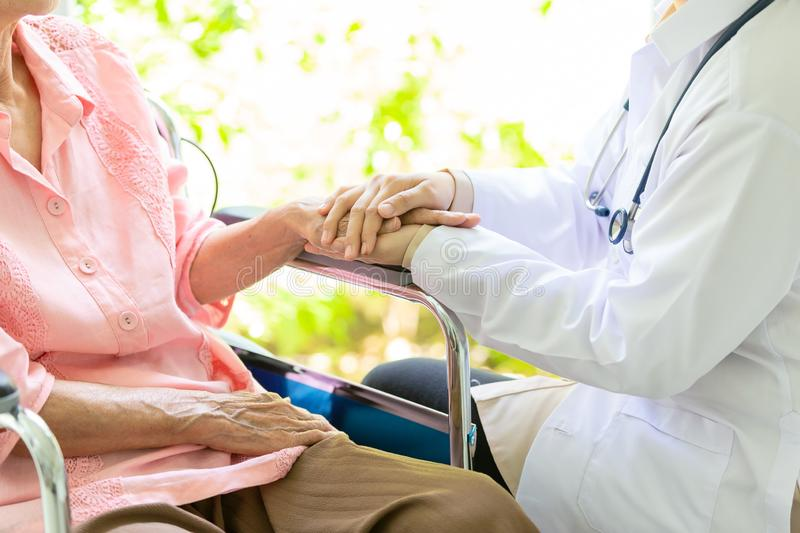 Closeup of hand medical female doctor or nurse holding senior patient hands and comforting her,.Caring caregiver woman supporting royalty free stock photos